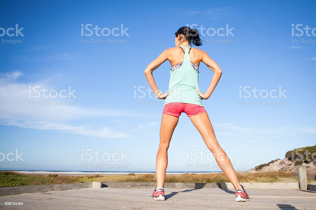 Athletic woman stretches before she runs stock photo