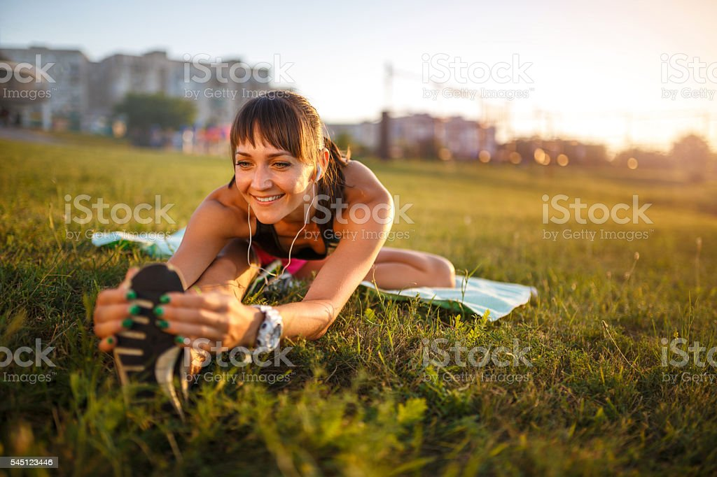 Athletic woman stretching her hamstring, legs exercise training stock photo