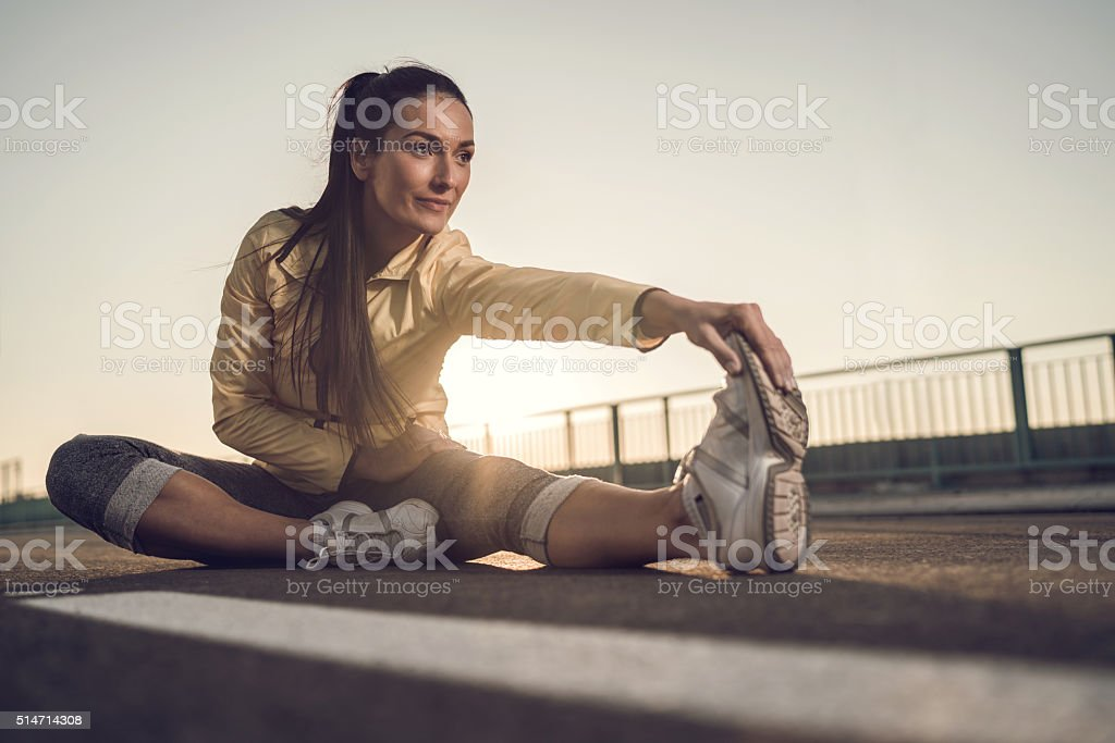 Athletic woman stretching her leg at sunset. stock photo