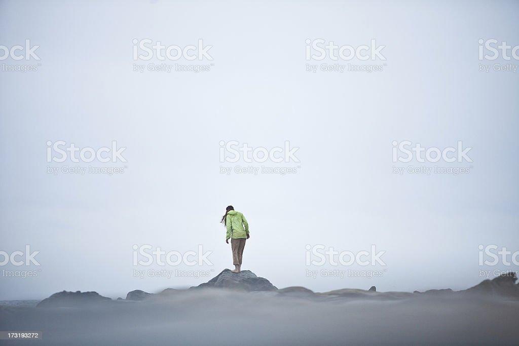 Athletic woman walking along a rocky coastline stock photo