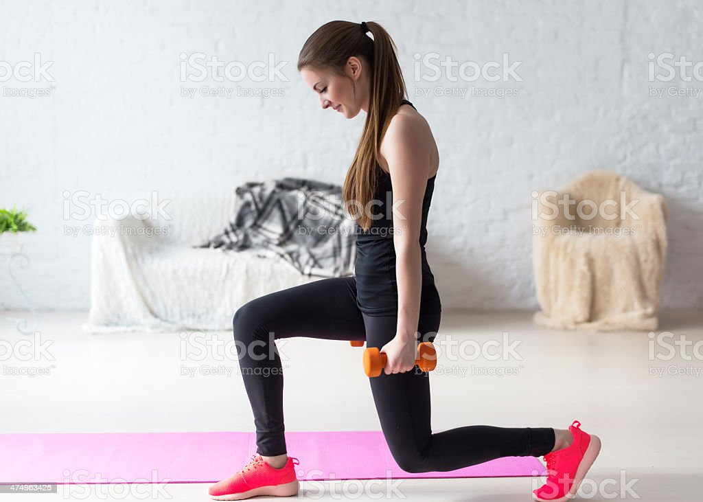 Athletic woman warming up doing weighted lunges with dumbbells workout stock photo