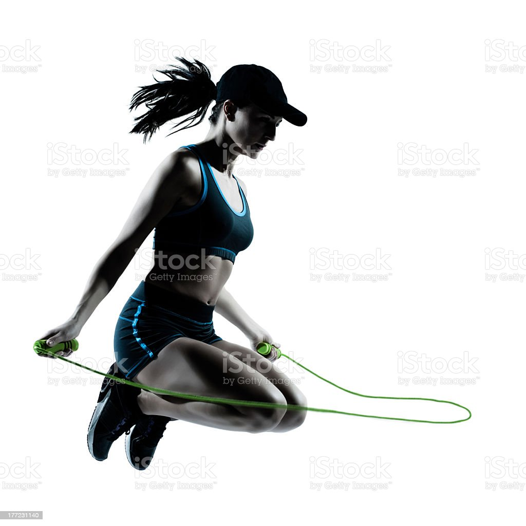 Athletic woman wearing sporty clothing jumping rope royalty-free stock photo