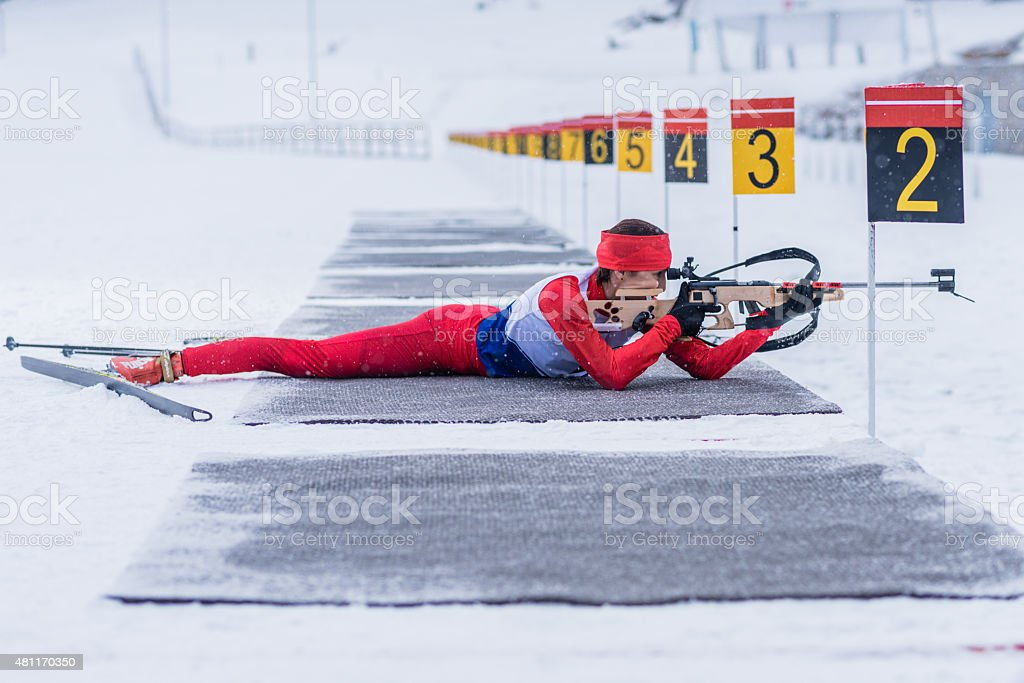 Athletic woman with biathlon rifle stock photo