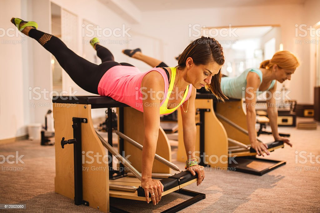 Athletic women exercising on Pilates stability chairs in health club. stock photo