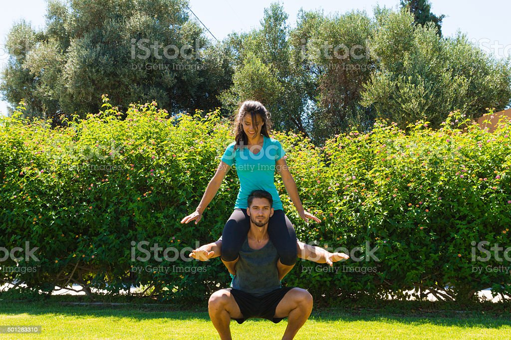 Athletic young couple doing fitness workout exercises at the park stock photo