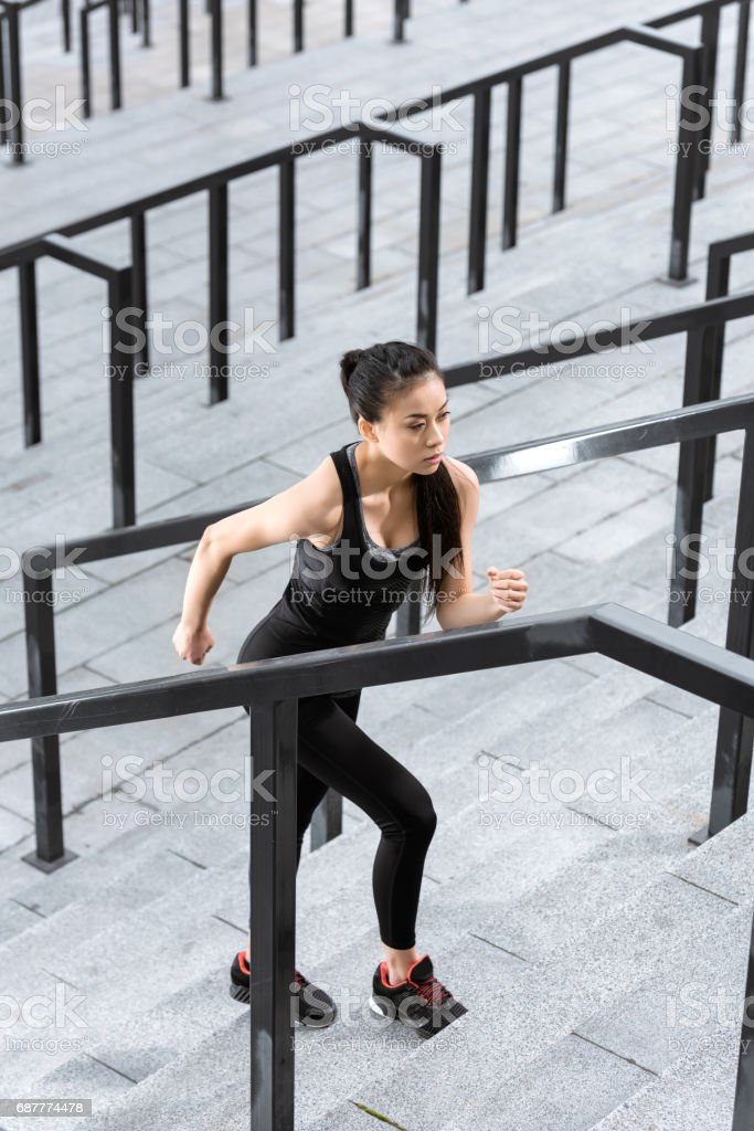Athletic young fitness woman in sportswear training on stadium stairs stock photo