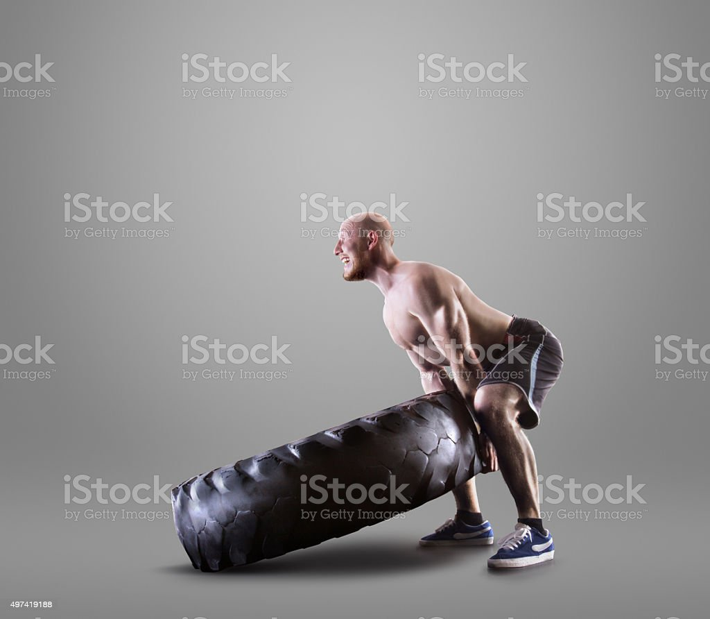 Athletic young man lifting a tire on gray studio background stock photo