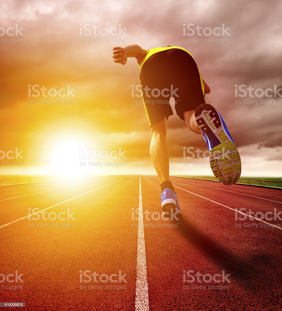 Athletic young man running on race track with sunset background stock photo