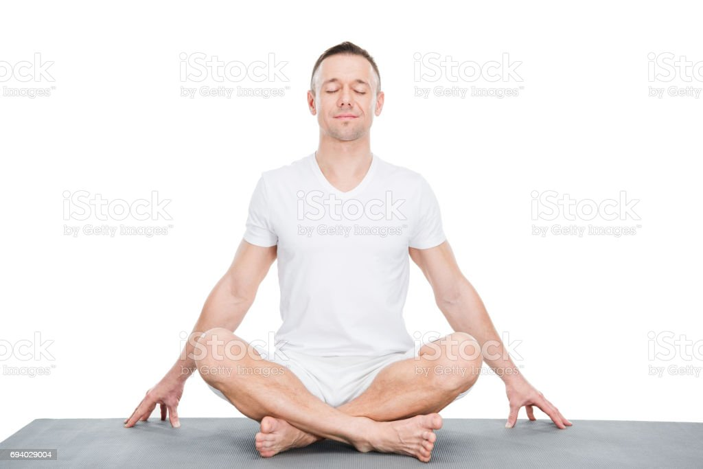 Athletic young man sitting on yoga mat and meditating in lotus position stock photo