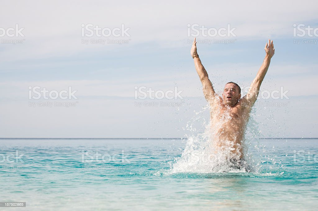 Athletic Young Man Swimmer Splashing Up from the Sea royalty-free stock photo