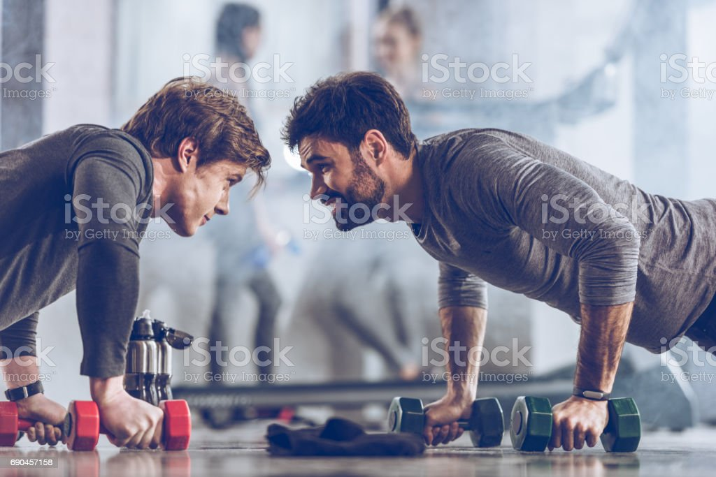 athletic young sportsmen doing push ups with dumbbells at the gym, gym workout concept stock photo