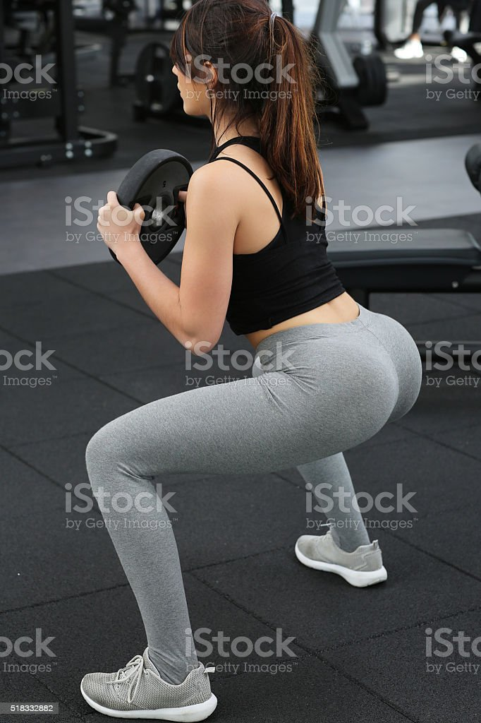 Athletic young woman fitness model doing squats stock photo