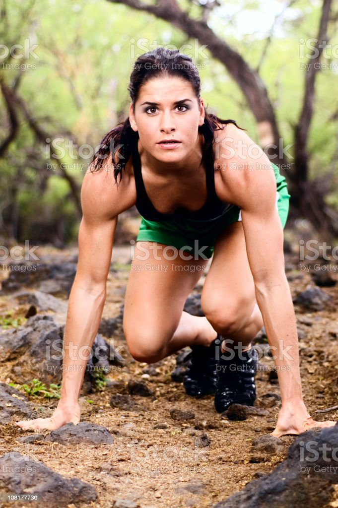 Athletic Young Woman Getting Ready to Run in Forest royalty-free stock photo