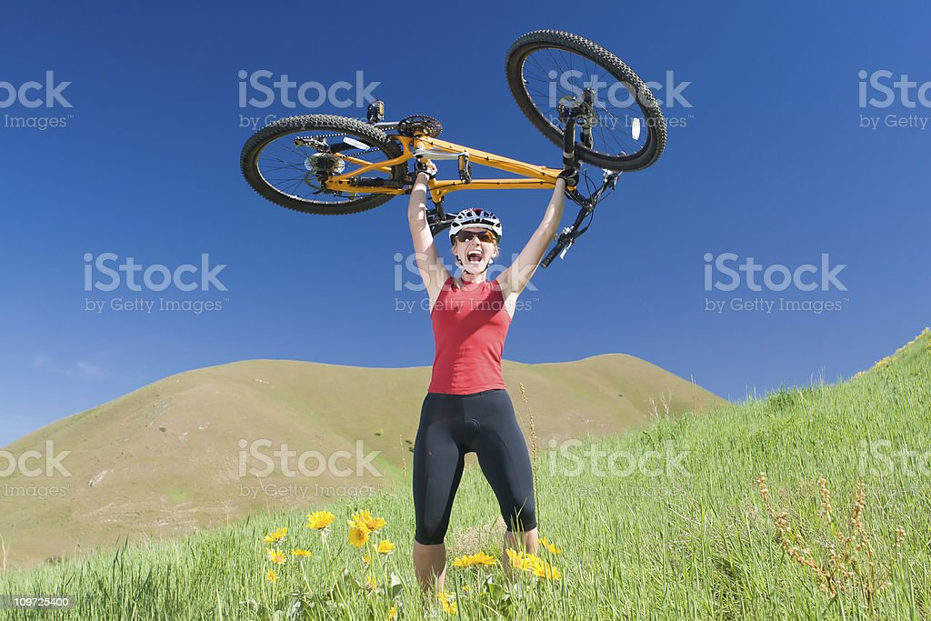 Athletic Young Woman Holding Bike Above Head on Hill royalty-free stock photo
