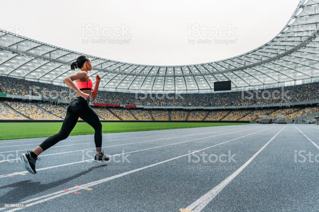 Athletic young woman in sportswear sprinting on running track stadium stock photo