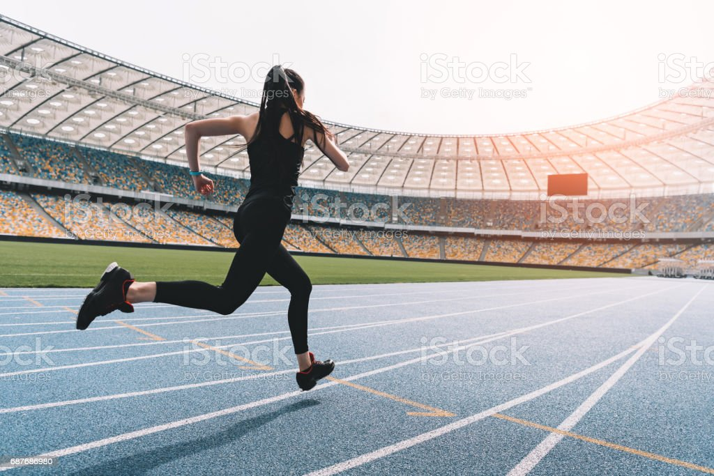 Athletic young woman in sportswear sprinting on running track stadium at sunset stock photo