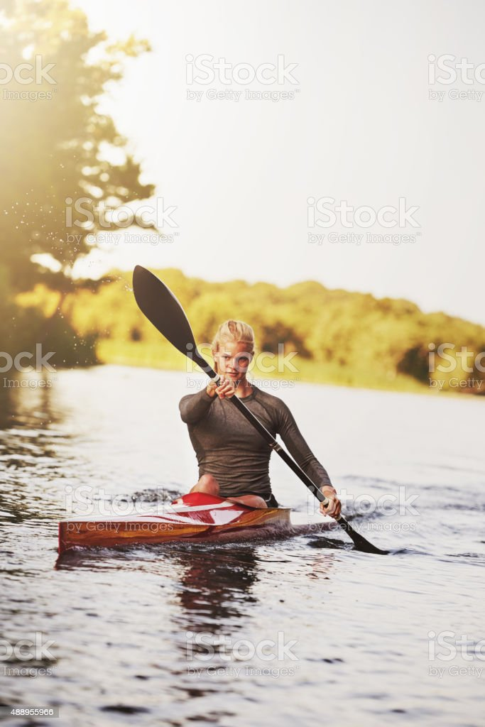 Athletic young woman paddling on lake in summer stock photo