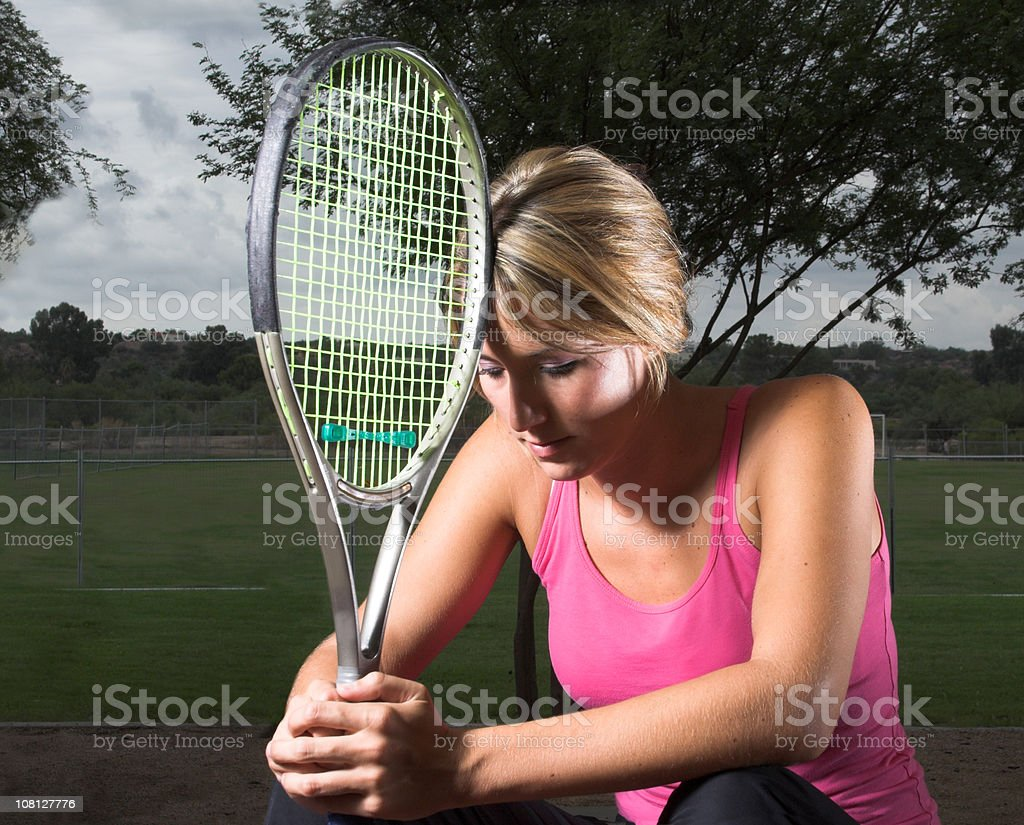 Athletic Young Woman Resting Head Against Tennis Racket royalty-free stock photo