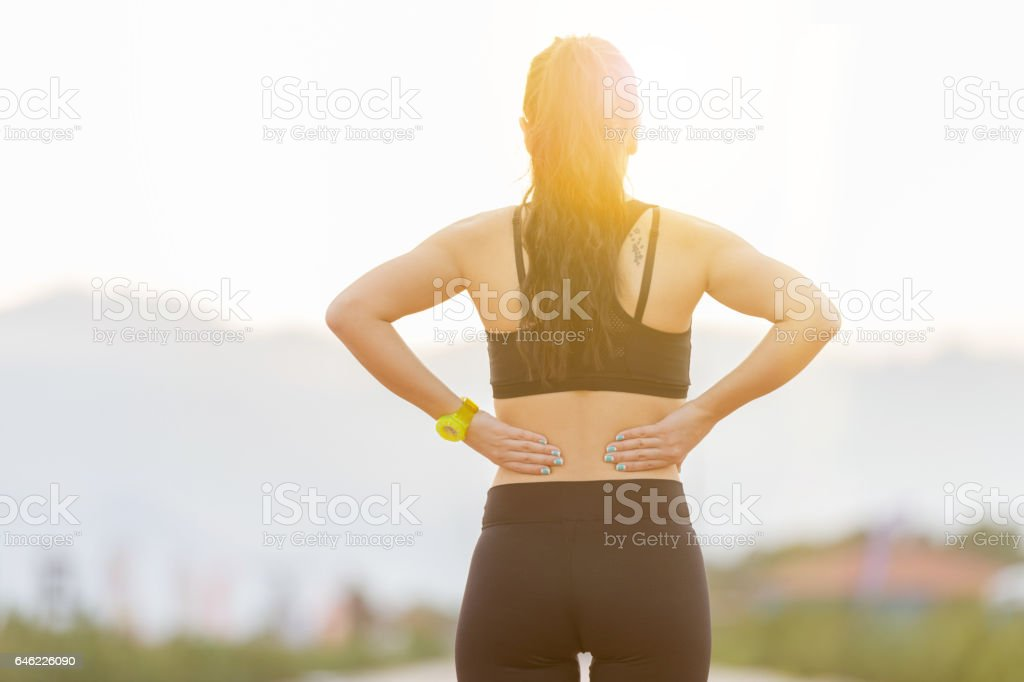 Athletic young woman rubbing muscles of lower back after jogging stock photo