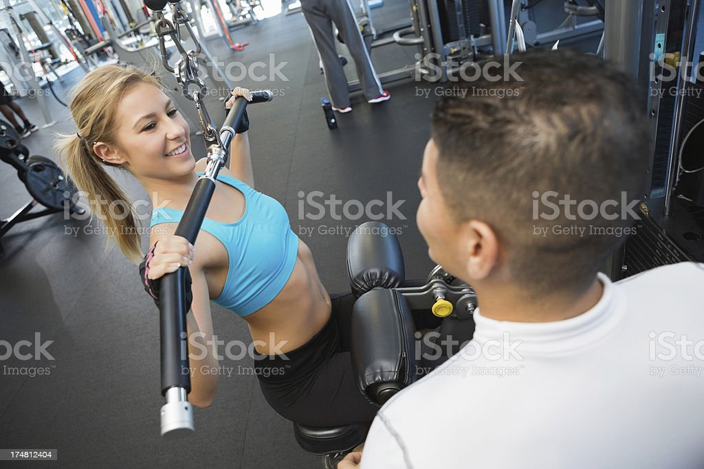 Athletic young woman working out with personal trainer in gym royalty-free stock photo