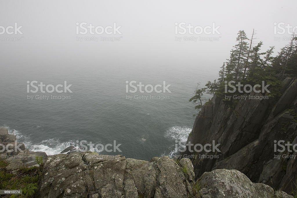 Atlantic Ocean beneath foggy cliffs stock photo