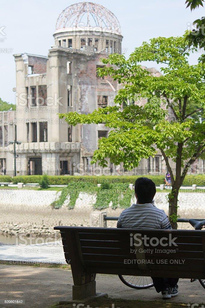 Atomic Bomb Dome (Hiroshima Peace Memorial), Japanese man on bench stock photo