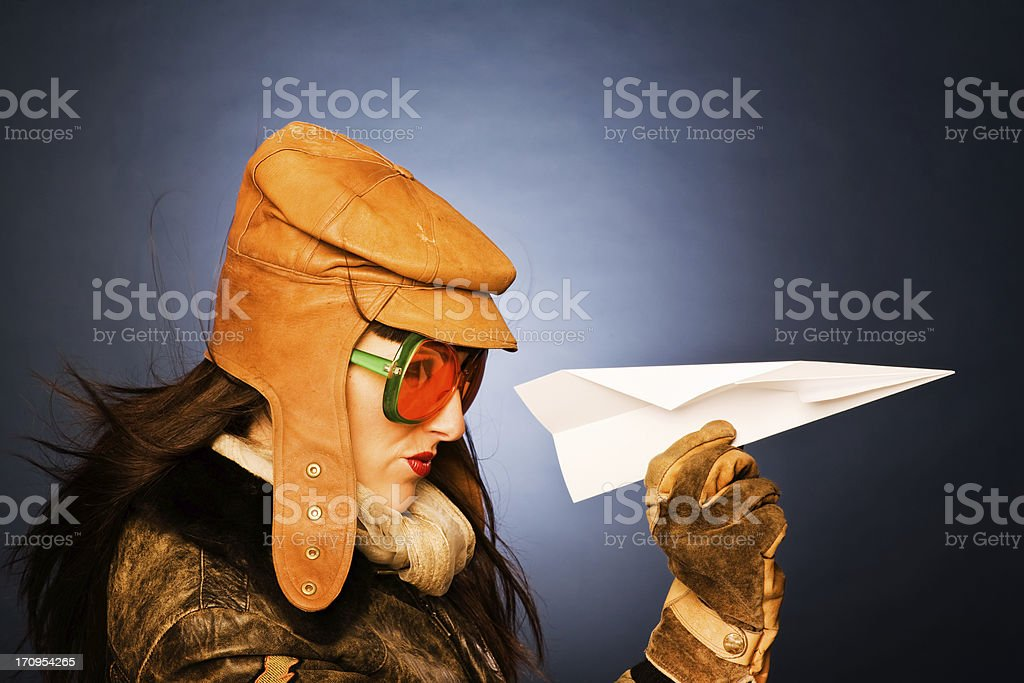 Atractive vintage woman  pilot playing with a paper plane. royalty-free stock photo