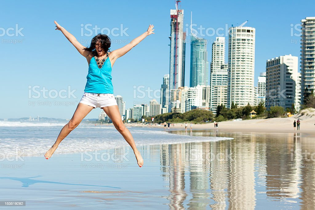 atractive woman jumps with joy on the beach stock photo