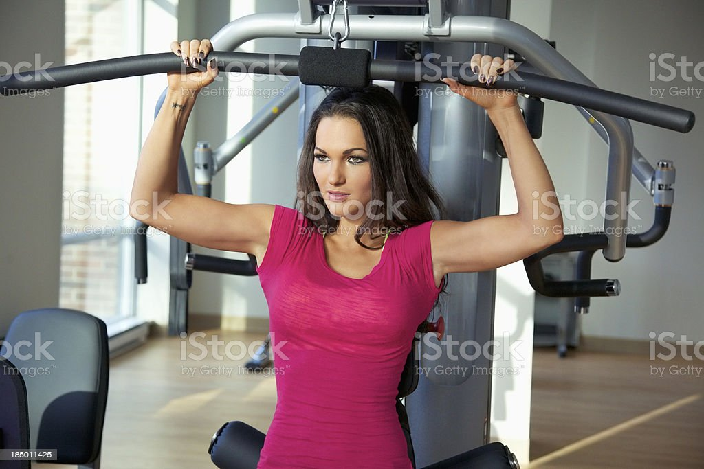 Atrtactive Young Woman Exercising on a Pectoral Machine royalty-free stock photo