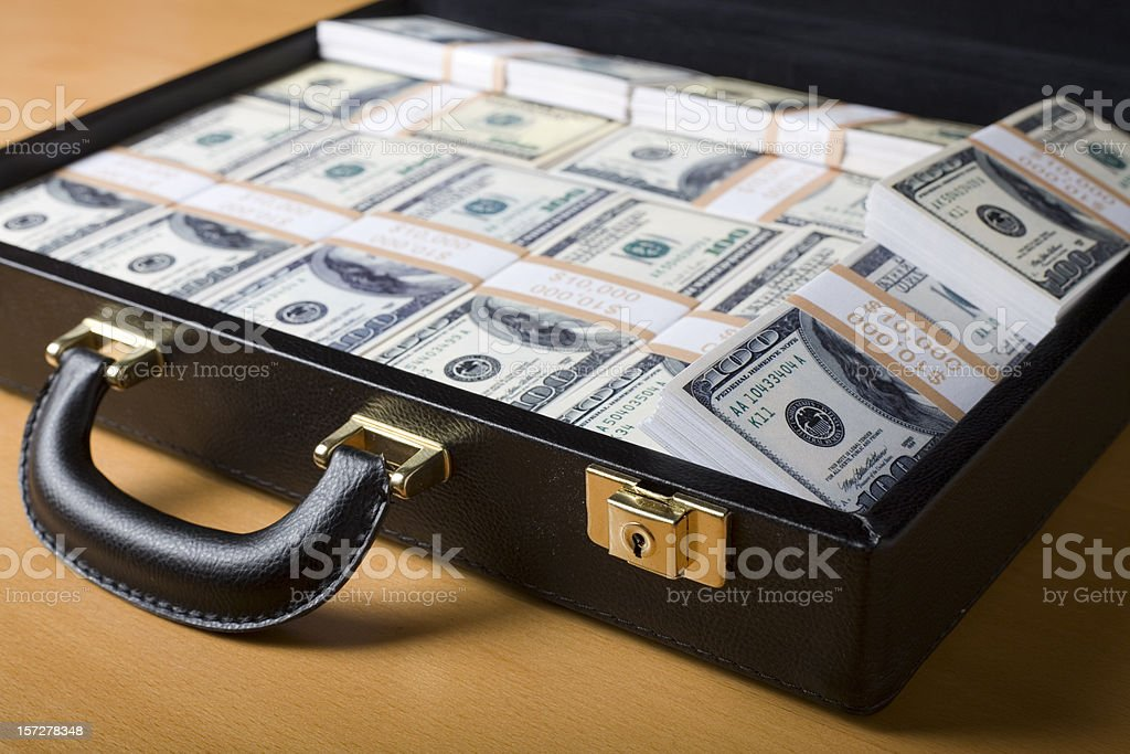 Attache full of money on the table royalty-free stock photo