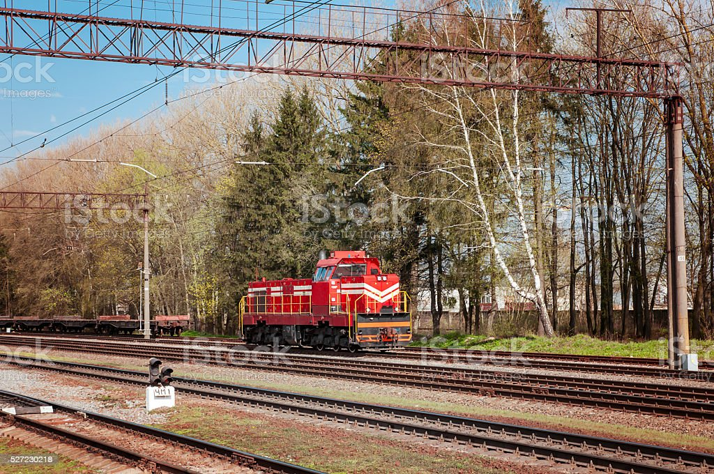 attached diesel locomotive is pulling freight wagons, spring stock photo
