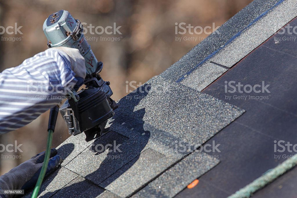 Attaching shingles to the roof. stock photo