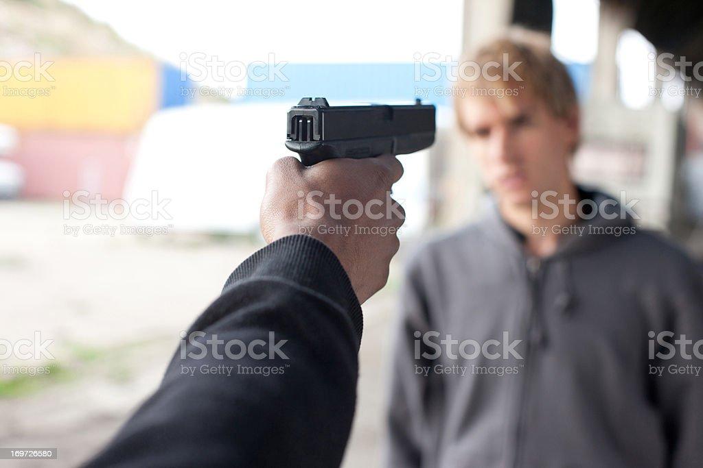 Attacker pointing gun at man stock photo