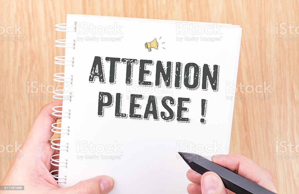 Attention please! word on white ring binder notebook with hand stock photo