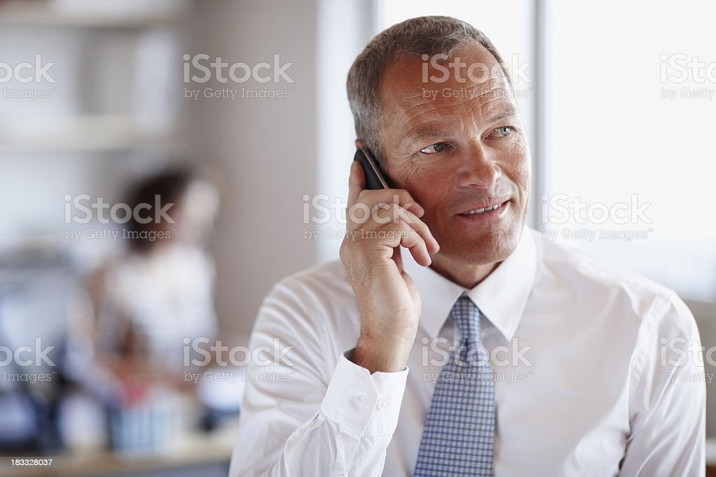 Attentive businessman on the phone with colleague in background royalty-free stock photo