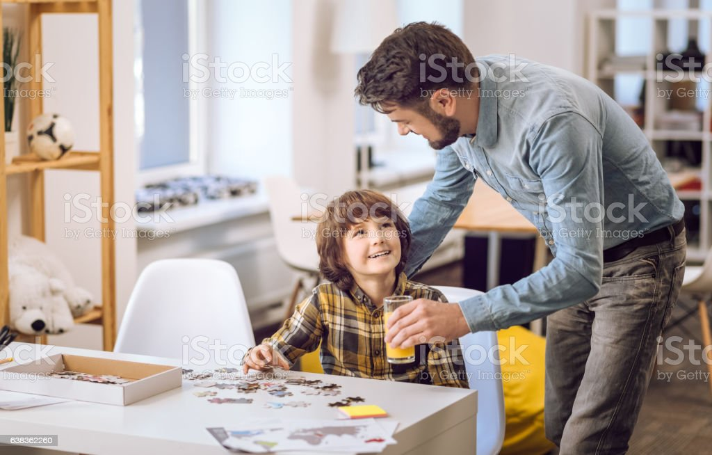 Attentive father giving a glass of juice to his son stock photo