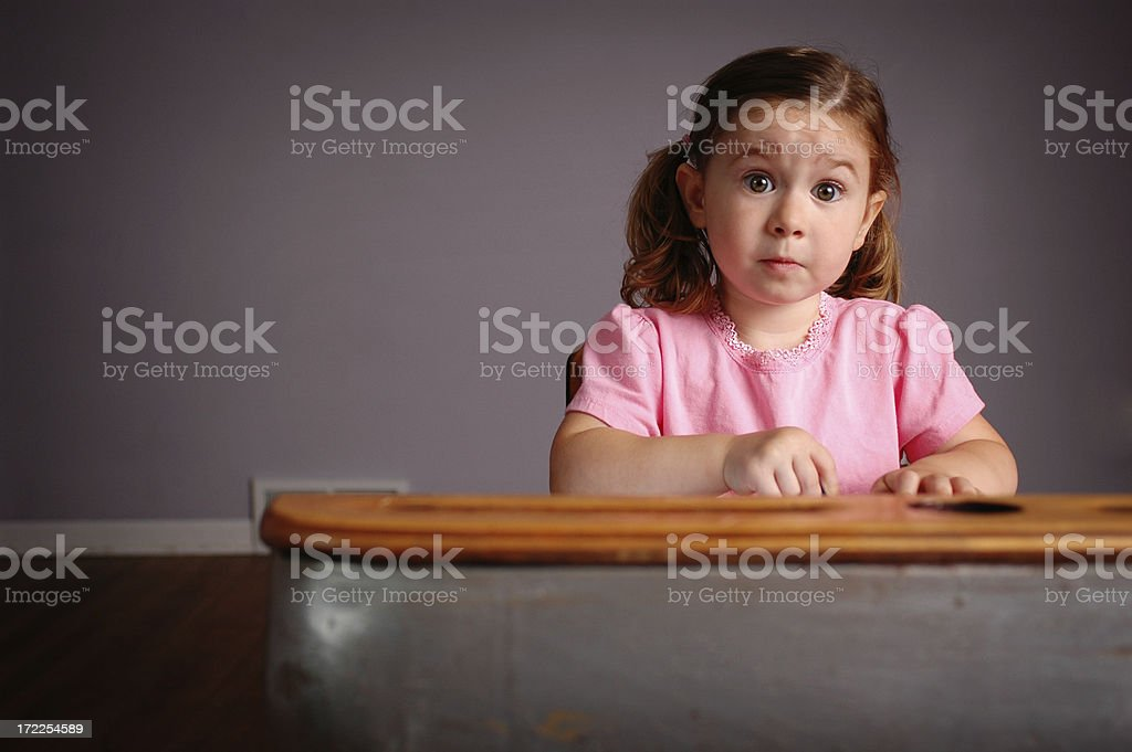 Attentive Little Girl Sitting in School Desk royalty-free stock photo