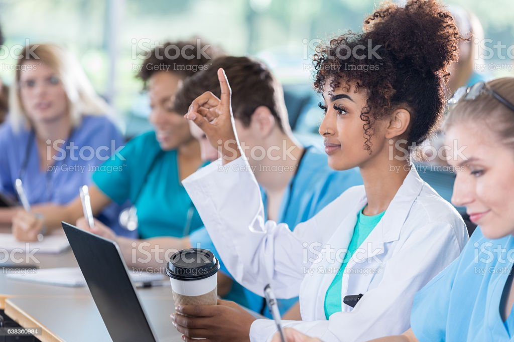 Attentive medical student asks question during class stock photo