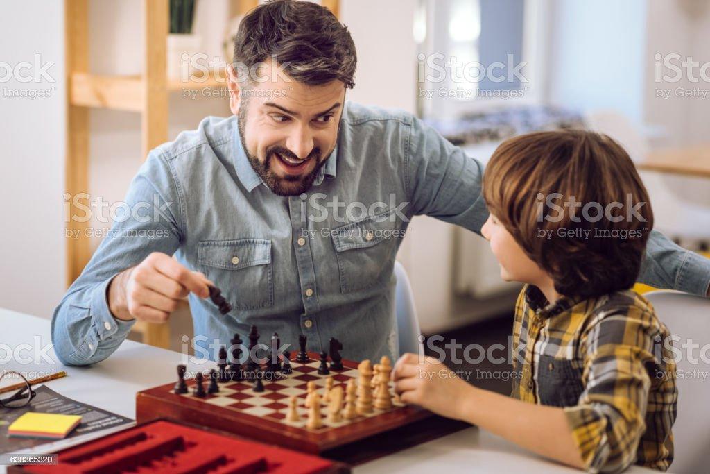 Attentive smart relatives playing chess stock photo