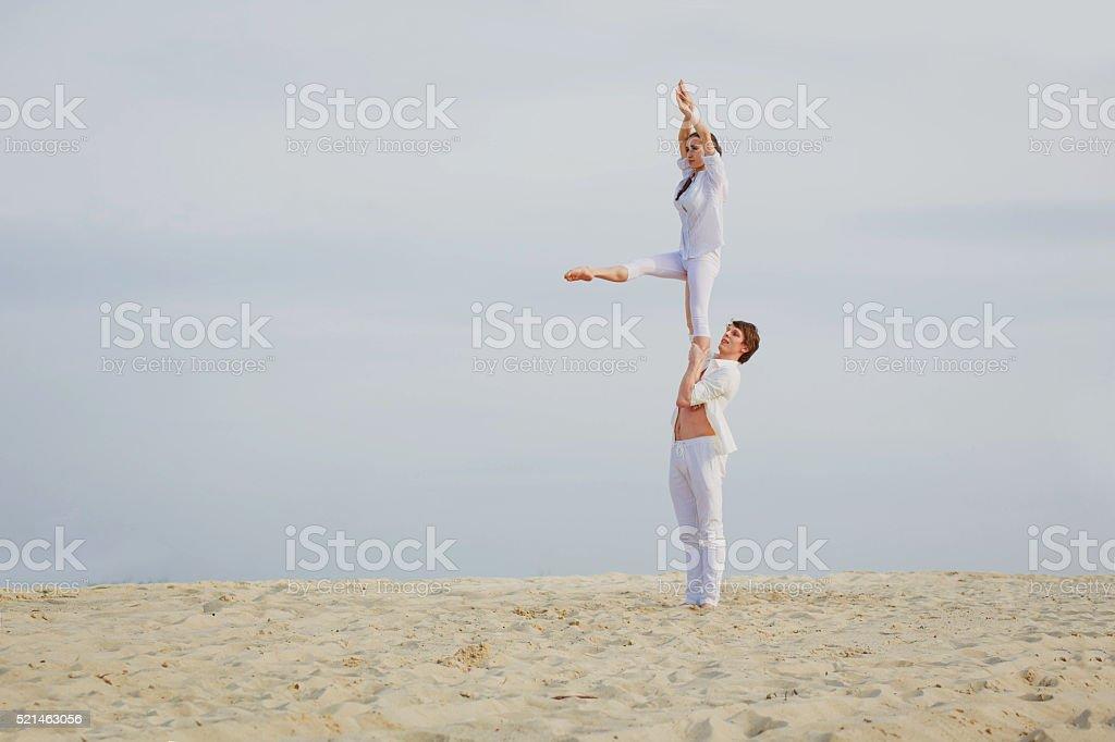 Attractive adult couple is balancing doing acro-yoga stock photo
