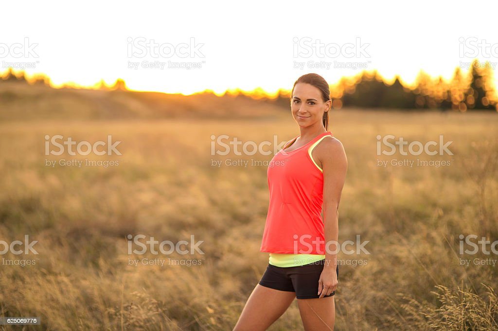 Attractive adult female athlete standing in tall grass trail running stock photo
