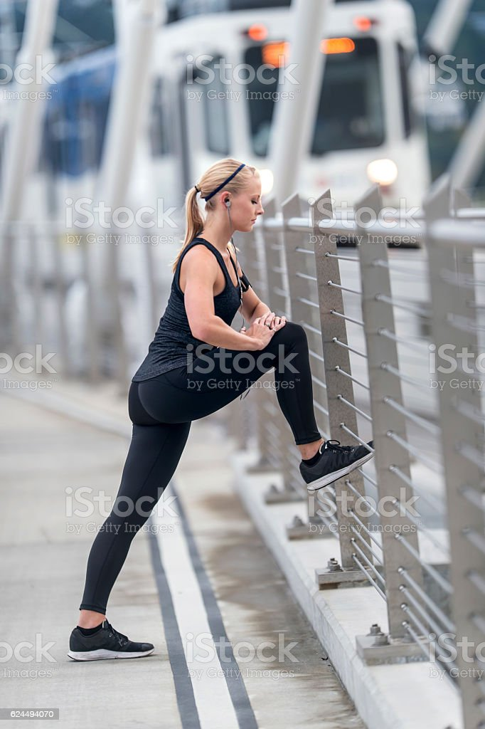 Attractive adult female athlete stretching and listening to music stock photo
