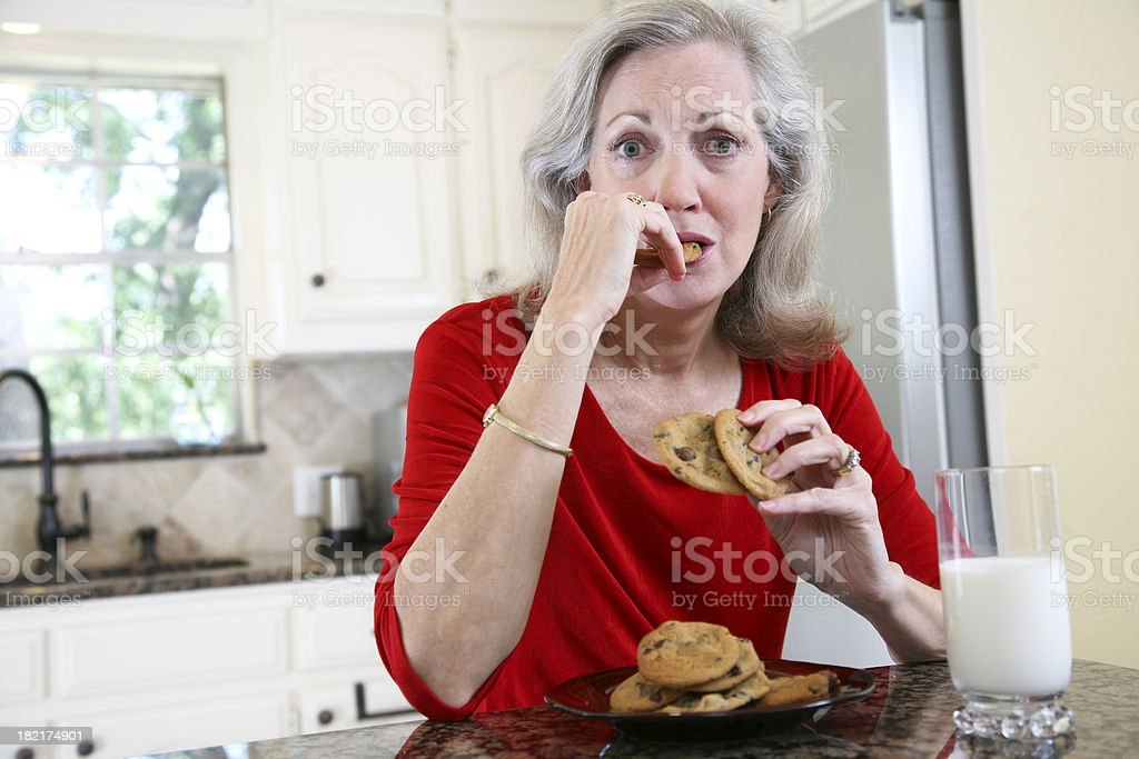 Attractive Adult Female Eating Cookies and Milk with Copy Space stock photo