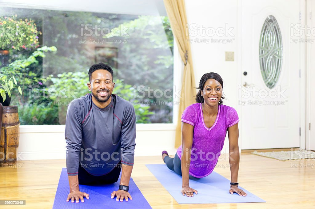 Attractive African american couple holding a yoga pose stock photo