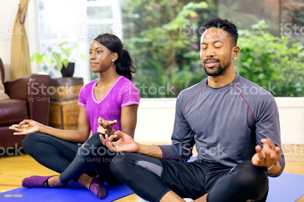 Attractive African american couple meditating stock photo