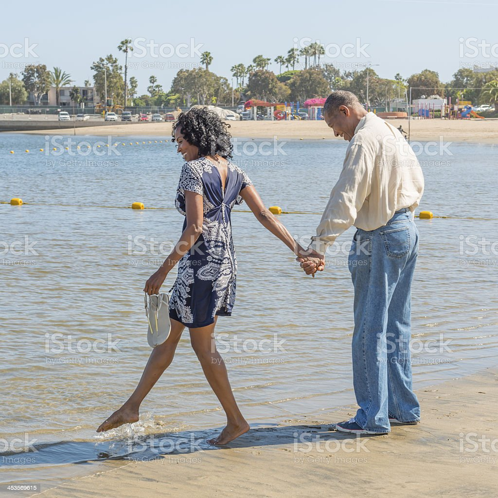 Attractive African American Couple on Beach testing water stock photo