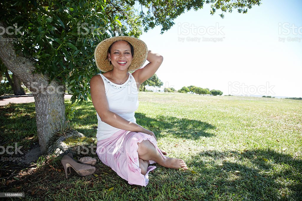Attractive african woman under shady tree stock photo