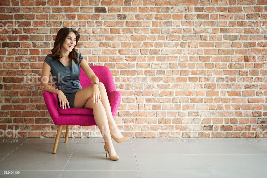 Attractive and cheerful woman in the armchair stock photo