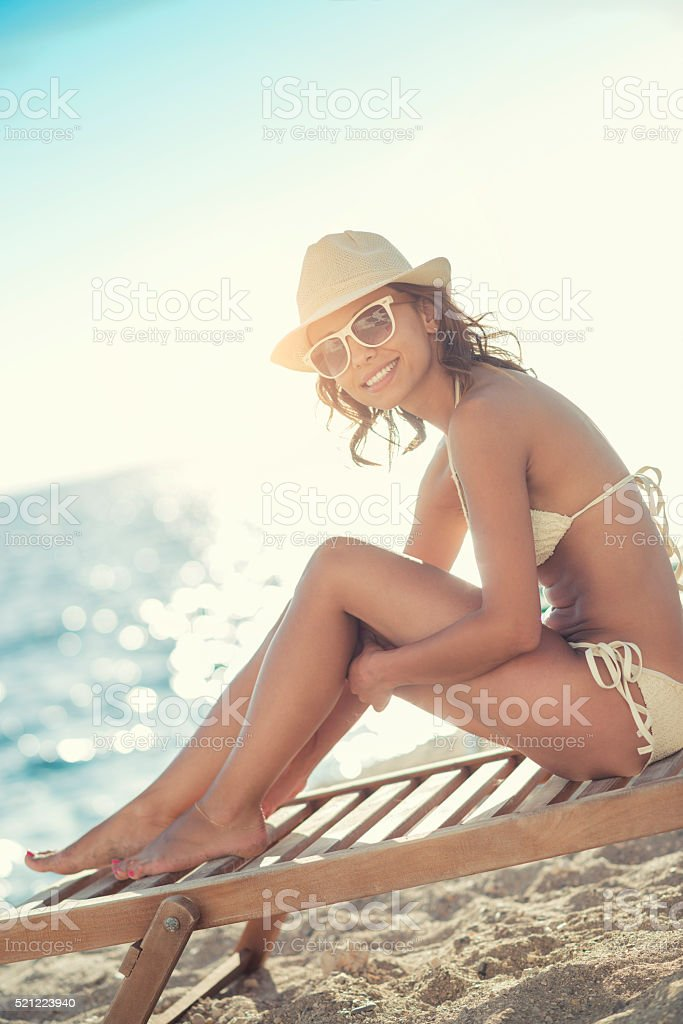 Attractive and Smiling Young Woman with Hat Sunbathing on Beach stock photo