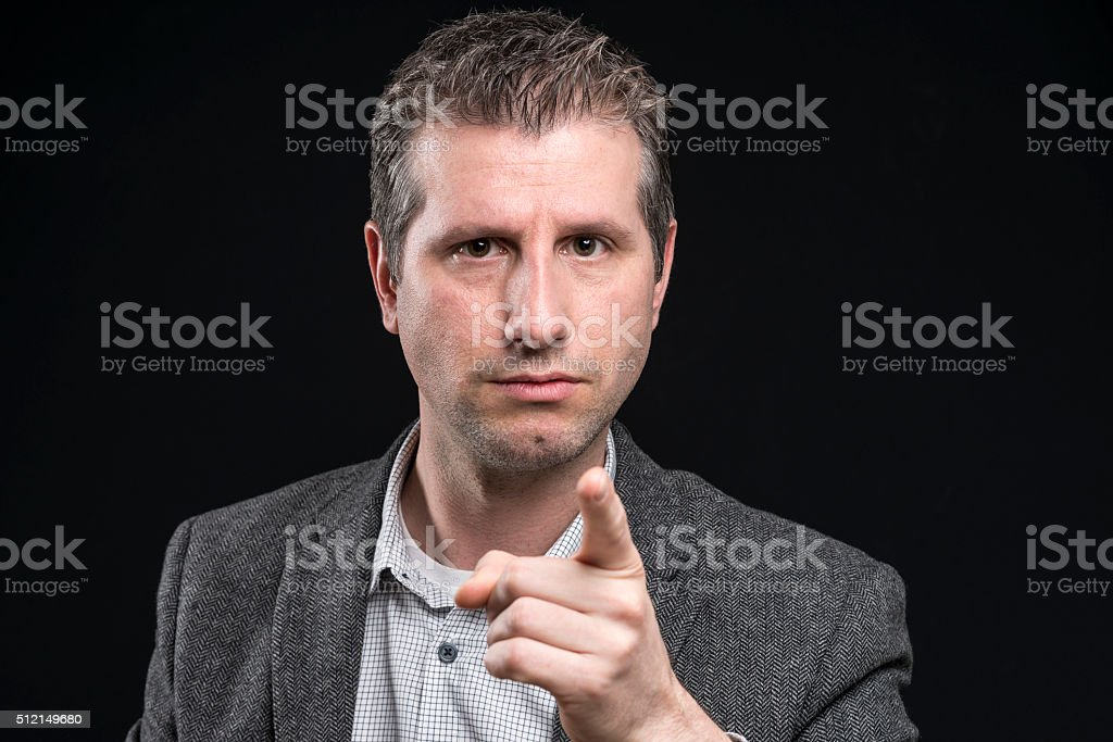 attractive angry businessman portrait pointing aggressive at camera stock photo
